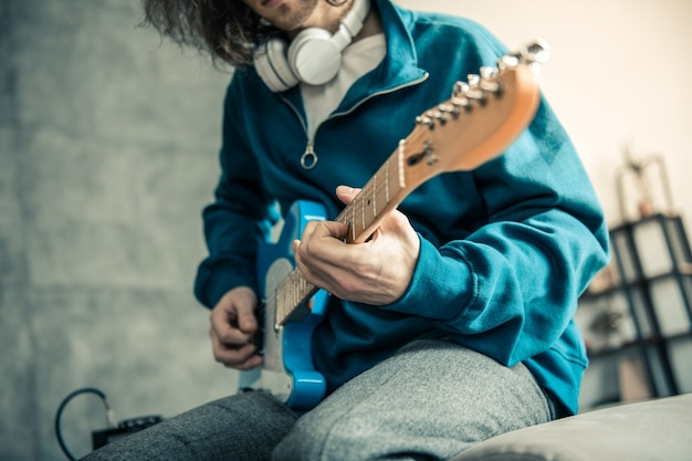 Jouer à la maison. jeune homme qualifié en sweat bleu montrant sa qualification tout en jouant de la musique
