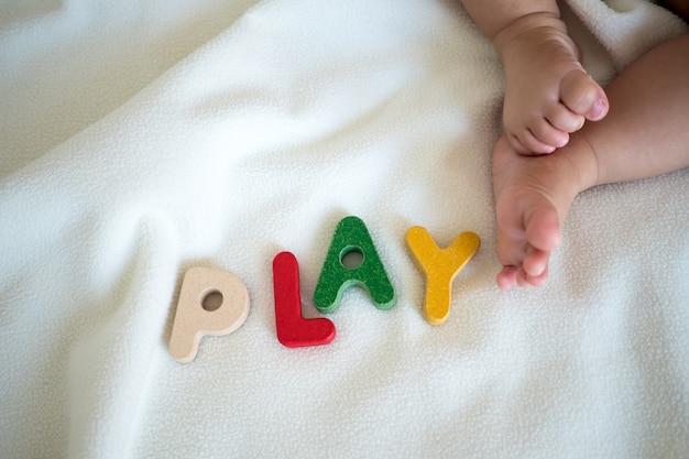 Jouer le mot en bois de texte sur la couverture avec pied enfant et copie de fond de l'espace