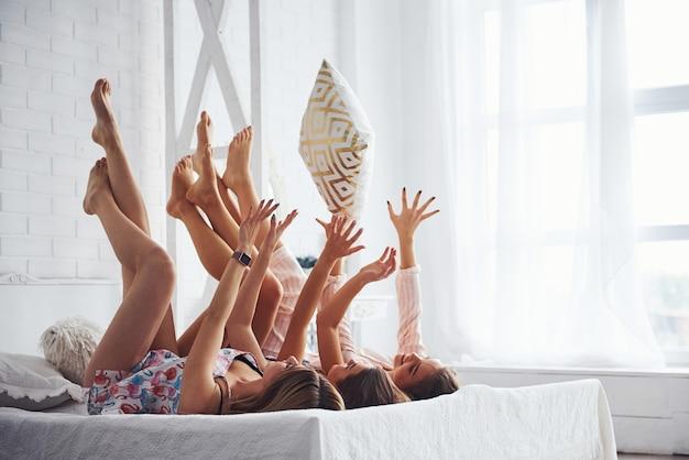 Jouer avec des oreillers. joyeuses amies s'amusant à une soirée pyjama dans la chambre.