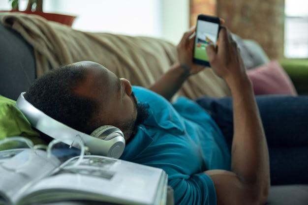 Jouer sur smartphone, surfer en ligne. homme afro-américain restant à la maison pendant la quarantaine à cause du coronavirus, propagation du covid-19. essayer de s'amuser. concept de soins de santé et de médecine.