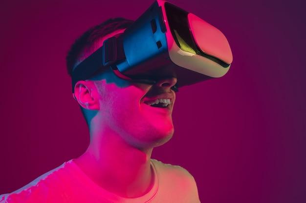 Jouer avec la vr, tirer, conduire. portrait d'un homme caucasien isolé sur un mur rose-violet à la lumière du néon. modèle masculin avec appareils. concept d'émotions humaines, expression faciale,