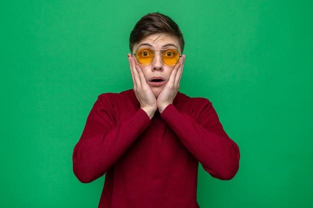 Joues couvertes de peur avec les mains jeune beau mec portant des lunettes isolées sur un mur vert
