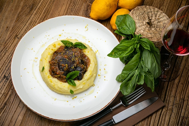 Les joues de veau sont préparées par le chef cuisinier, les herbes et le zeste de citron sur une assiette. sur une table en bois