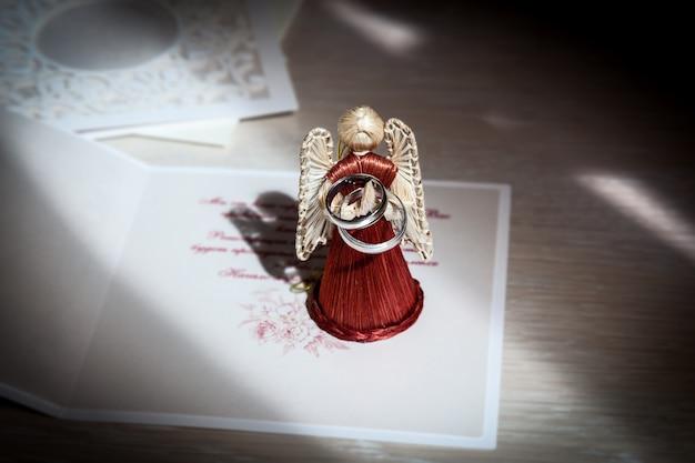 Jouet d'ange fait de paille tenant deux anneaux de mariage jeune