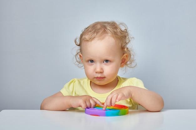Jouet anti-stress populaire pop it. enfant jouant avec le jouet pop it fidget. enfance heureuse, jeux éducatifs populaires.