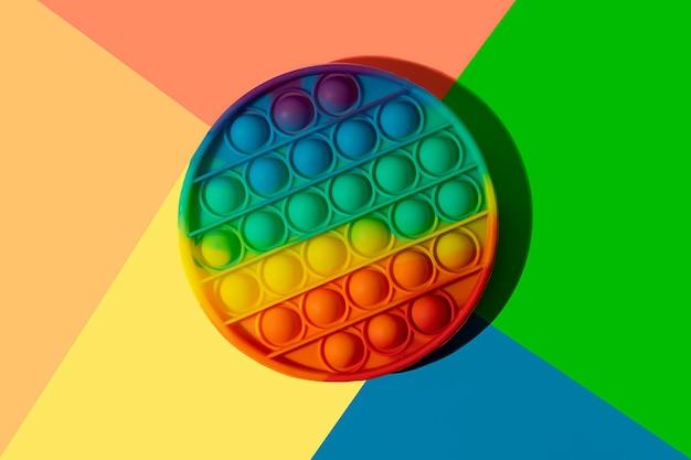 Le jouet anti-stress rond en silicone apparaît sur le fond arc-en-ciel coloré.