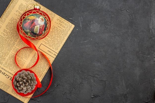Jouet d'arbre de noël vue de dessus en ruban sur papier journal sur une surface sombre