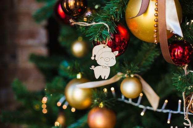 Jouet en bois de noël sous la forme d'un symbole de l'année approchante-cochon accroché à un arbre de noël de fête