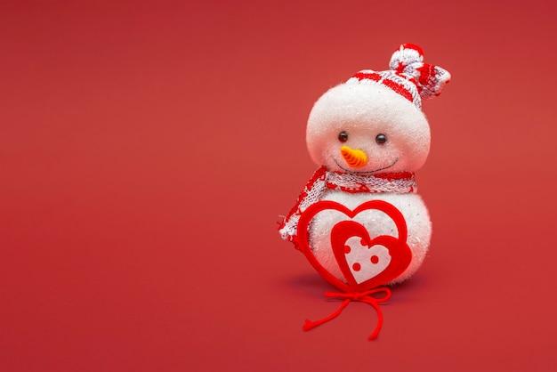 Jouet bonhomme de neige isolé sur fond rouge avec espace de copie