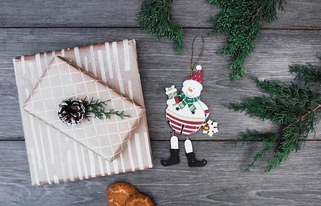 Jouet bonhomme de neige près de cadeaux dans des emballages avec accroche, brindilles et biscuits