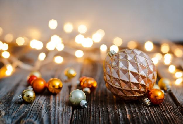 Jouet boule de sapin de noël posé sur une table en bois contre un bokeh de lumières de noël.