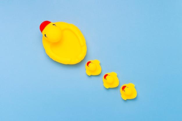 Jouet en caoutchouc de couleur jaune mama-canard et petits canetons sur fond bleu. le concept de soins maternels et d'amour pour les enfants, l'éducation et l'éducation des enfants. mise à plat, vue de dessus