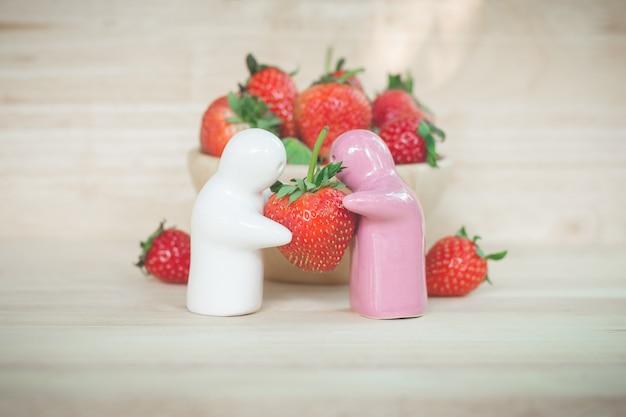 Jouet en céramique donnant une fraise aux couples pour leur amour