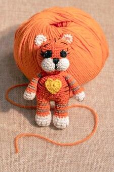Jouet chaton tricoté orange avec une pelote de fil, travaux d'aiguille à la maison.
