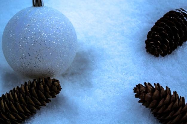 Le jouet et les cônes du nouvel an se trouvent dans la neige