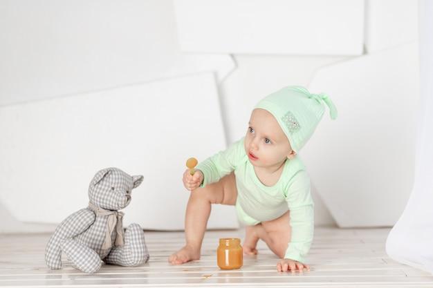 Jouet cuillère d'alimentation bébé en body vert, concept d'alimentation et de nourriture pour bébé