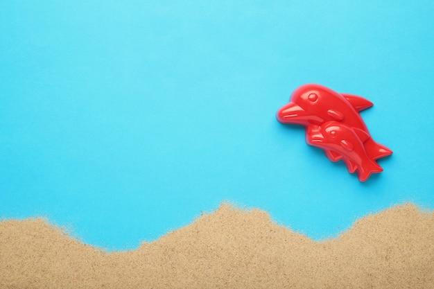 Jouet dauphin rouge avec du sable sur fond bleu. composition d'été. vue de dessus