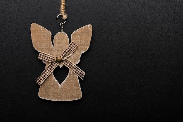 Jouet décoratif en bois ange de noël avec un coeur sur fond noir