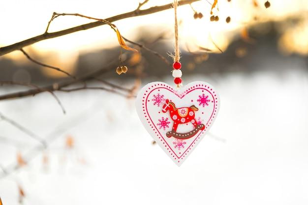 Jouet de décoration de noël ou de la saint-valentin en forme de coeur suspendu à une branche d'arbre avec de la neige sur le fond