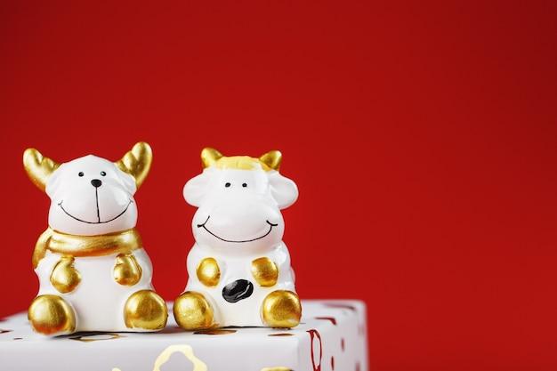 Jouet du nouvel an d'un taureau et d'une vache avec un cadeau sur fond rouge