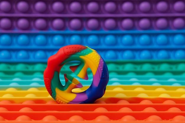 Jouet éducatif tendance snapperz sur fond de jouet en silicone coloré pop it extenseur coloré