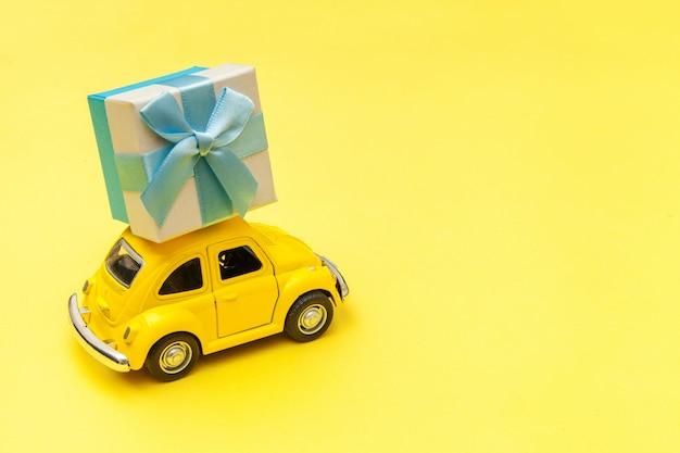 Jouet jaune voiture livrant coffret cadeau sur le toit isolé sur fond jaune tendance