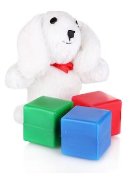 Jouet lapin assis et cubes de couleur isolés sur blanc