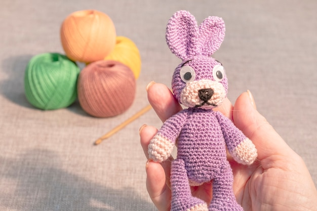 Un jouet de lapin dans la main d'une femme sur fond de boules à tricoter. hobbies jouets au crochet.