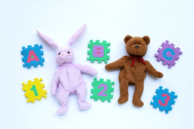 Jouet de lapin et ours en peluche avec puzzle alphabet anglais et chiffres sur blanc. concept de l'éducation, espace copie