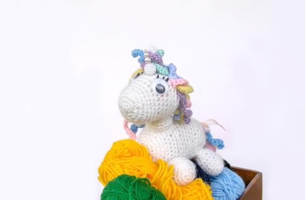 Jouet licorne au crochet fait à la main et fil colorul dans une boîte en bois sur fond blanc.