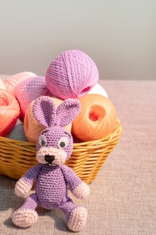 Jouet de lièvre tricoté lilas avec un panier d'écheveaux de fil, travaux d'aiguille à la maison.