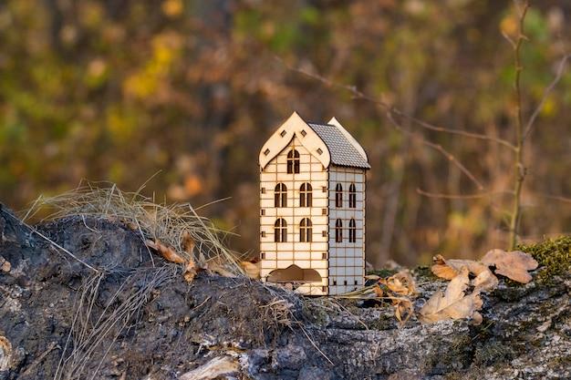 Jouet maison en bois dans la forêt à l'automne. logement dans la nature