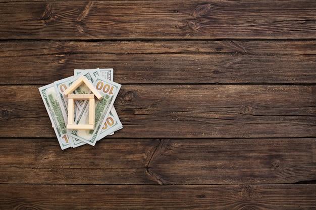 Jouet maison en bois avec des dollars sur fond de bois ancien