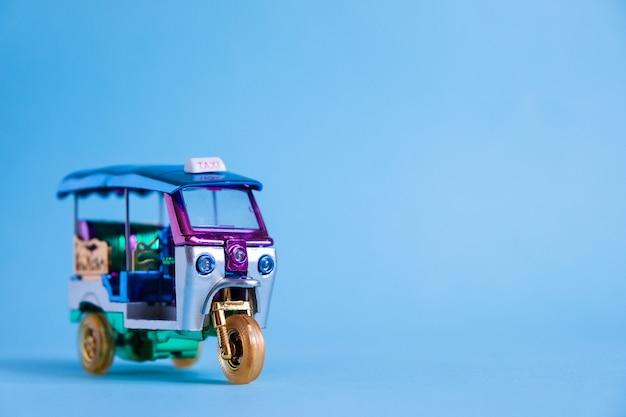 Jouet modèle tuk tuk isolé sur mur bleu. taxi traditionnel thaïlandais à bangkok en thaïlande. souvenir