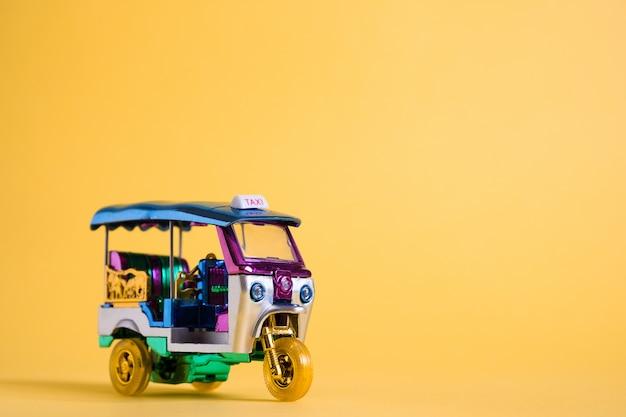 Jouet modèle tuk tuk isolé sur mur jaune. taxi traditionnel thaïlandais à bangkok en thaïlande. souvenir