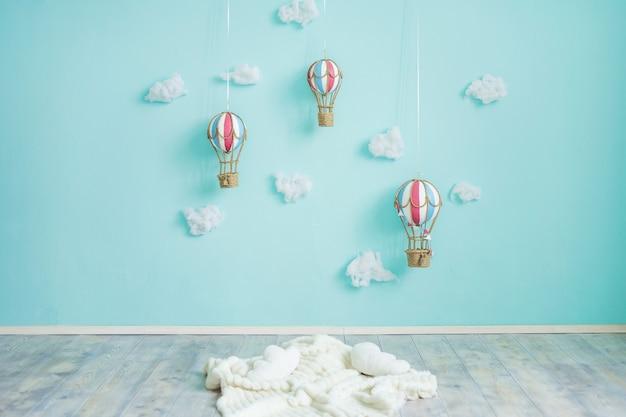 Jouet montgolfières et nuages sur un mur bleu