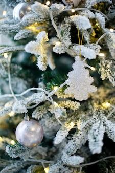 Jouet de noël blanc accroché sur la branche de sapin enneigé détail