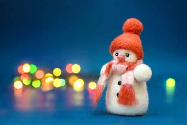 Jouet de noël bonhomme de neige en laine feutrée dans un chapeau d'hiver rouge
