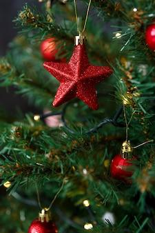 Jouet de noël en forme d'étoile accrochée à une branche de lumières bokeh de guirlandes