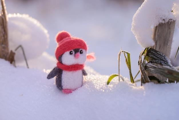 Jouet de noël en laine feutrée mignon petit pingouin dans un chapeau rouge d'hiver et une écharpe sur une journée d'hiver ensoleillée