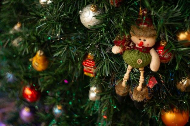 Un jouet de noël sous la forme d'un bonhomme de neige est suspendu à un arbre de noël artificiel avec des lumières vives colorées.