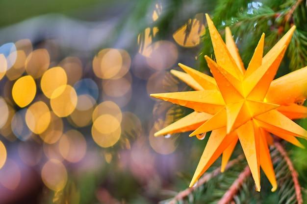 Jouet de noël sous la forme d'une étoile jaune sur une branche d'un arbre de noël