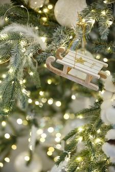 Jouet de noël traîneau suspendu à une branche d'épinette avec guirlande