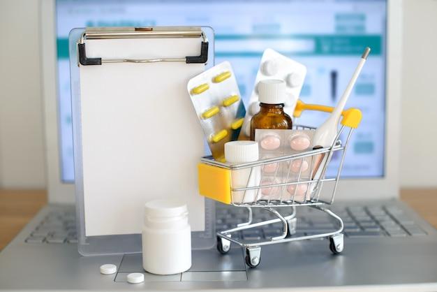 Jouet de panier d'achat avec des médicaments en face de l'écran de l'ordinateur portable avec le site web de la pharmacie sur elle