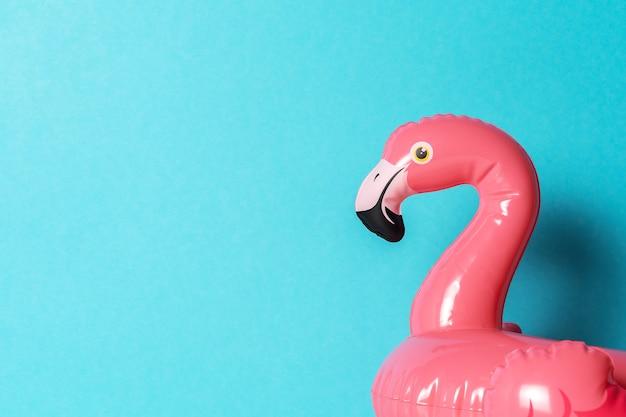 Jouet de piscine gonflable flamant rose sur un bleu.
