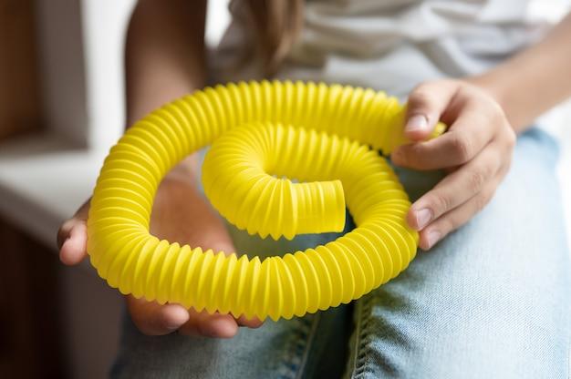Jouet en plastique anti-stress sensoriel tube pop dans les mains d'un enfant. une petite fille heureuse joue avec un jouet poptube à la maison. enfants tenant et jouant de la couleur jaune du tube pop, tendance 2021 année