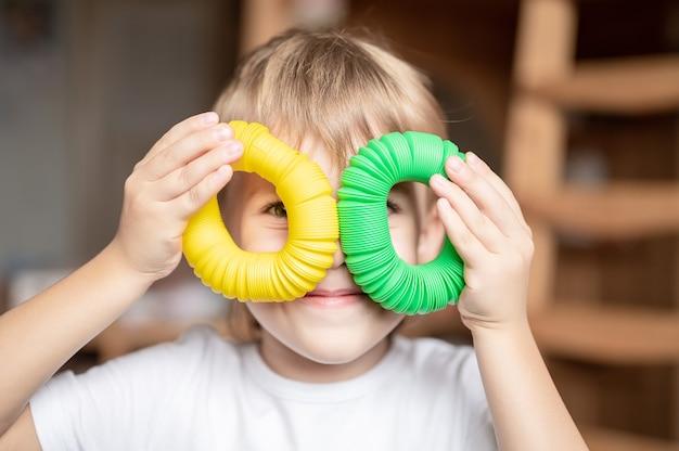 Jouet en plastique anti-stress sensoriel tube pop dans les mains des enfants. un petit garçon heureux joue avec un jouet poptube à la maison. enfants tenant et jouant pop tube couleur jaune et verte, tendance 2021 année