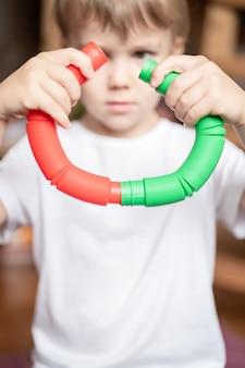 Jouet en plastique anti-stress sensoriel tube pop dans les mains des enfants. un petit garçon heureux joue avec un jouet poptube à la maison. enfants tenant et jouant pop tube couleur rouge et verte, tendance 2021 année