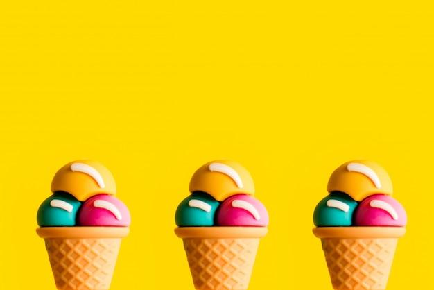 Jouet en plastique de cornet de crème glacée assortis de saveurs sur fond jaune