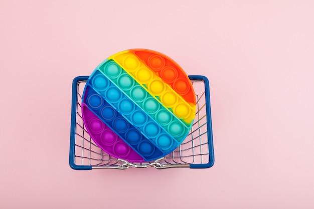 Jouet pop it anti-stress coloré en silicone pour enfant dans la vue de dessus du panier push pop bubble